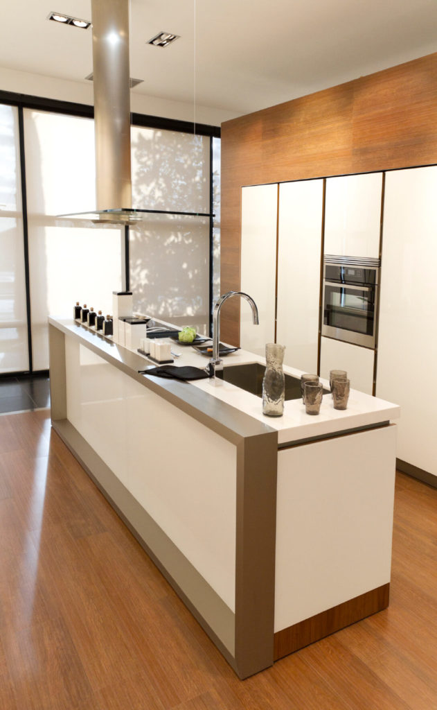 Another modern and minimalist small kitchen with hard wood floors and white cabinetry without visible pulls. The seamless windows that cover the rear of the room have pull-down shades for privacy.