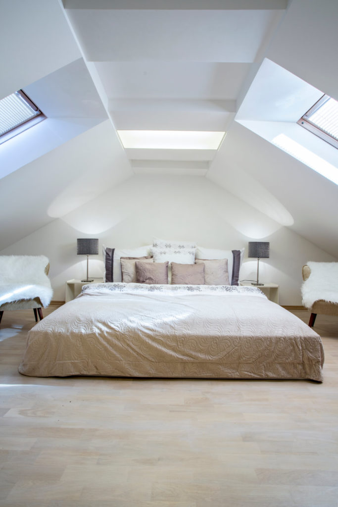 A trio of skylights pour light in from different angles onto the spacious bed. A light color scheme includes natural light hardwood floors. The space is anchored in the complementary color palette of neutrals and natural wood.
