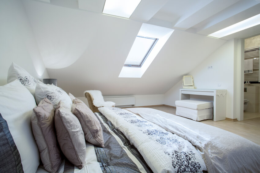 A bedroom's exposed beams frame the skylight. An additional window pours in light on the far angled wall. The bed is facing the adjacent bathroom, tucked into the sloping space.