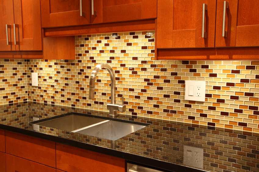A Glass Tile Backsplash With Accents Of Gold And Red.