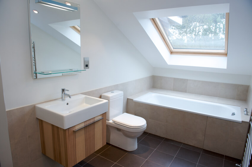 A minimalist attic bathroom with a natural wood vanity and a tile-enclosed soaking tub beneath the skylight. A small glass shelf is attached to the mirror, making up for some of the storage lost around the sink.