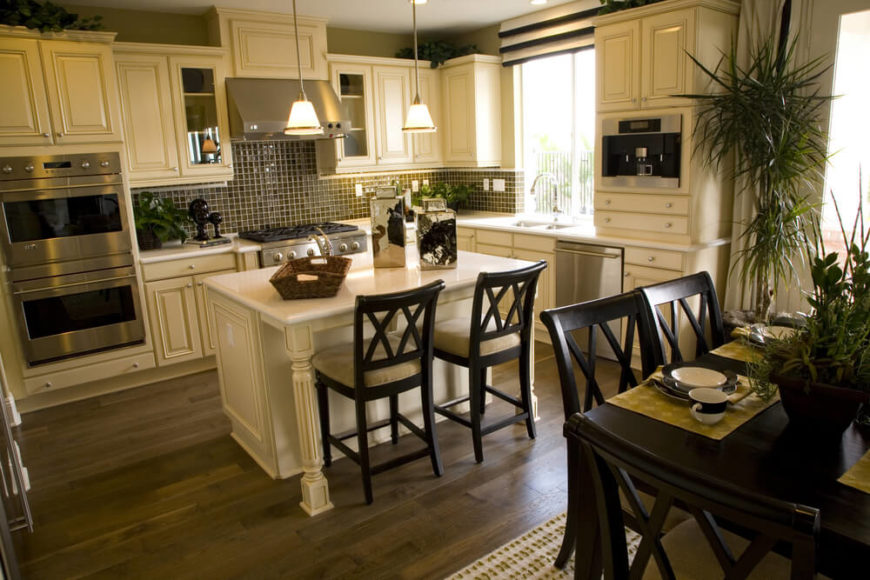 A White Kitchen With Glass Tile Backsplash And Hardwood Flooring. A Small  Kitchen Island