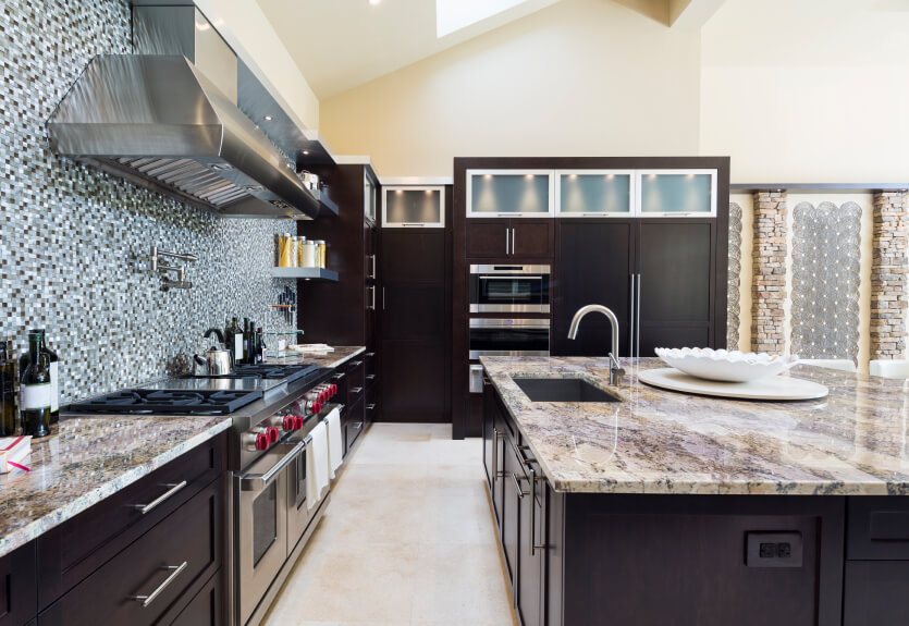 A Dark Kitchen With Marble Countertops And A Large Amount Of Glass Mosaic  Tile On The