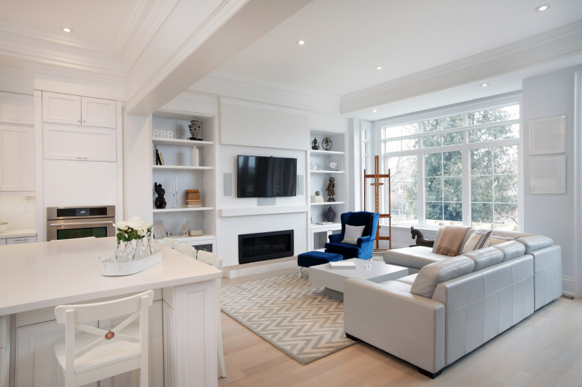 An open-concept living room dominated by white. The adjacent eat-in kitchen is also in a pristine white from floor to ceiling. The light wood floor is covered by a light gray chevron rug. Near the expansive windows is an art easel and built in shelving on either side of the fireplace and television. The bright blue armchair and ottoman is a striking addition to the neutral and white room.