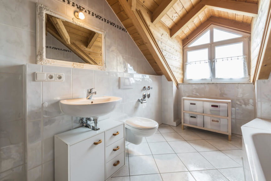 A white bathroom with gorgeous natural wood ceilings. The glossy white tile is pervasive throughout the spacious room, which includes a wall mounted sink, soaking tub, and a small chest of drawers.