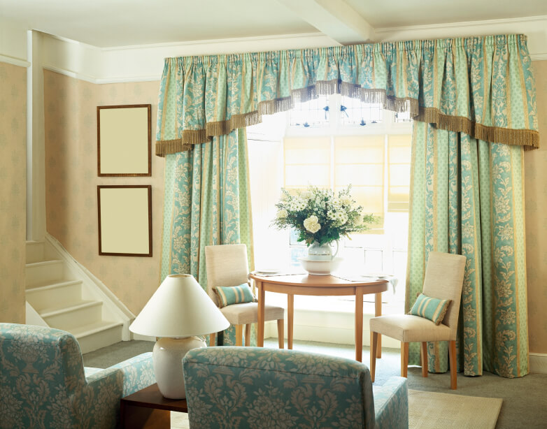A traditional, small living room with a set of stairs leading up to the next floor. The pattern of the armchairs is closely matched to the heavy, traditional curtains with a fringed valance. Near the window is a small chair topped by a lush bouquet and two small armless chairs. This space makes use of a wide hallway to create a sitting room.