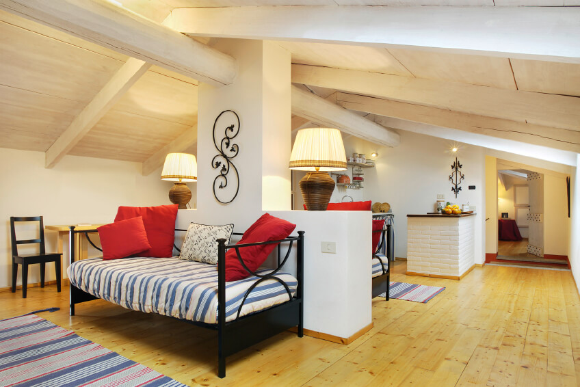 This attic has been converted into a multi-functional apartment space, with a pair of daybeds on either side of the support wall and an additional full bedroom on the other side of the attic.
