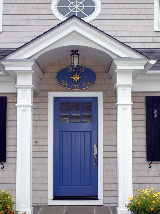 "This house has a white stoop roof which is supported by two rectangular pillars. Hanging in the ceiling of the roof is a door lamp. It has a blue front door with glass window panels. The door has a nickel door lock and handle. It also has a white door frame. Just above the door there is a round blue sign which says: ""Bliss By the Sea."""