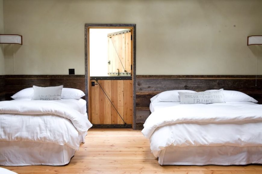 A close up of the bunk room, showing the natural pine flooring and the light gray throw pillows with French text.