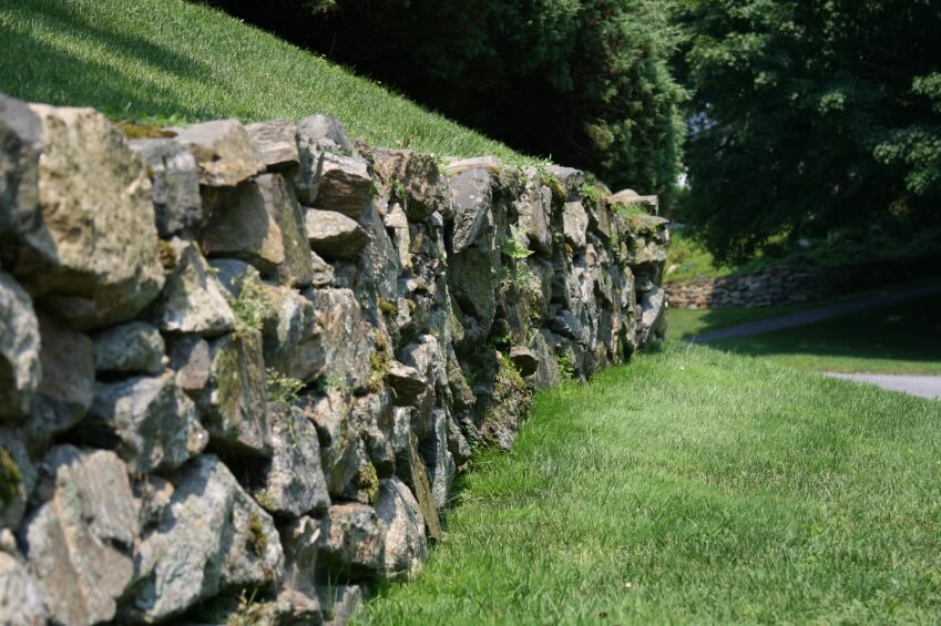 A more country, rustic retaining wall by the side of a paved pathway, creating a terrace up the large hillside. Moss grows on the old stones, marking this wall as well aged.