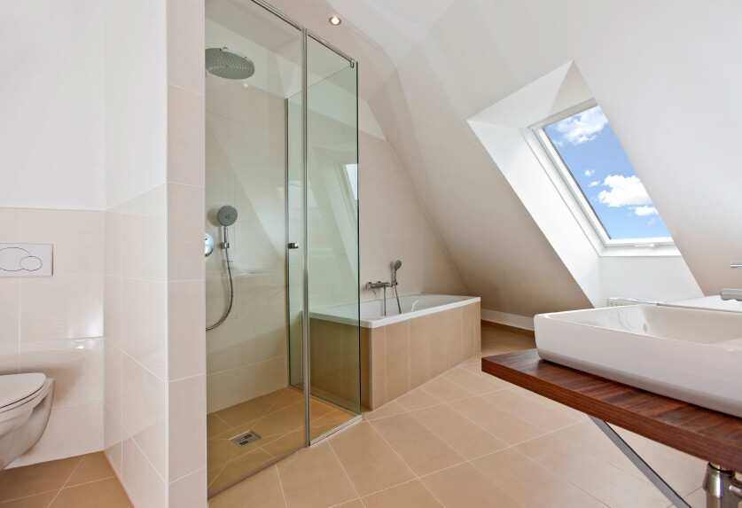 An attic bathroom with a fantastic skylight and plenty of space. Vessel sinks sit on a minimalist vanity in wood and chrome. The glass-enclosed shower is next to the deep, luxurious soaking tub enclosed in the warm-toned tile of the floor. A small wall helps provide some privacy for the commode.