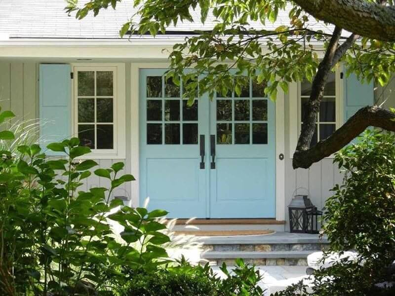 This home has a light teal and blue front exterior. It features a light blue double door entrance with glass panels. There are two glass framed windows in front. A doorbell is also installed on the white door frame. There is a lot of green foliage in front of the house.