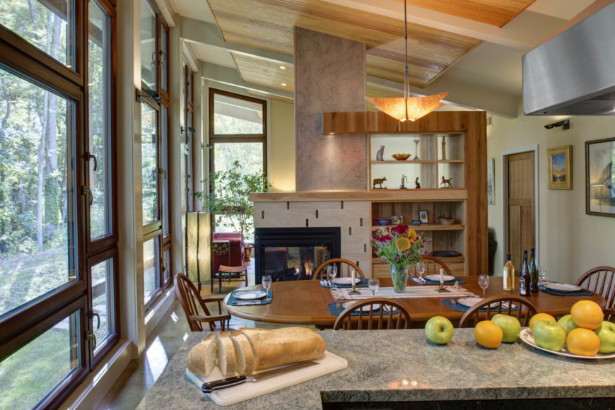 The view over the dining room from the kitchen island shows the fireplace that is open to both the dining room and the living room beyond.