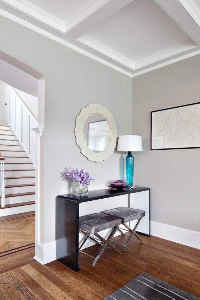A small desk area with velvet seating and glass vase decorations sits on the other side of the doorframe from the shelving unit. Above the desk is a circular mirror in ivory. The table lamp is in a beautiful bold turquoise.