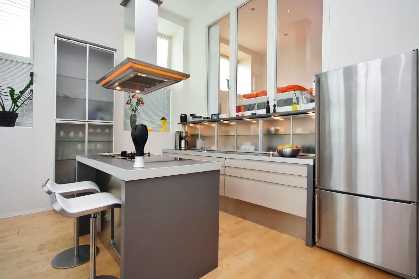 A modern kitchen with frosted-glass cabinetry and shelving on the side of the room and behind the main preparation area. The cooktop is in the kitchen island, leaving more countertop space for preparation.
