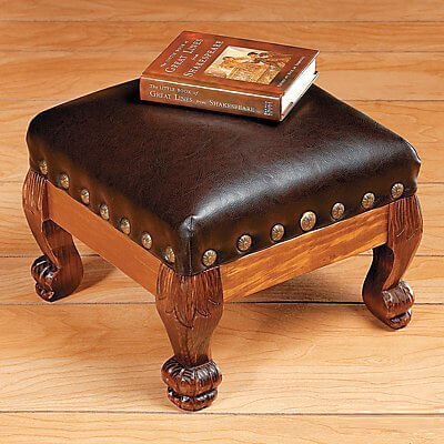 This leather upholstered ottoman features a traditional, luxurious style with claw foot carved wooden legs and detailed nailhead trim around the cushioning.