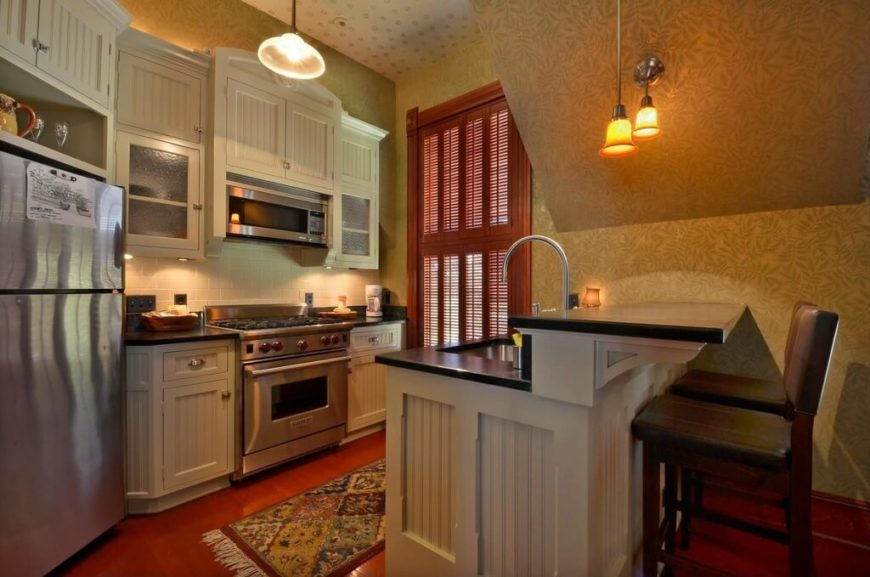 A Small Kitchen With A Two Tier Island And Bead Board Accents On The Cabinet