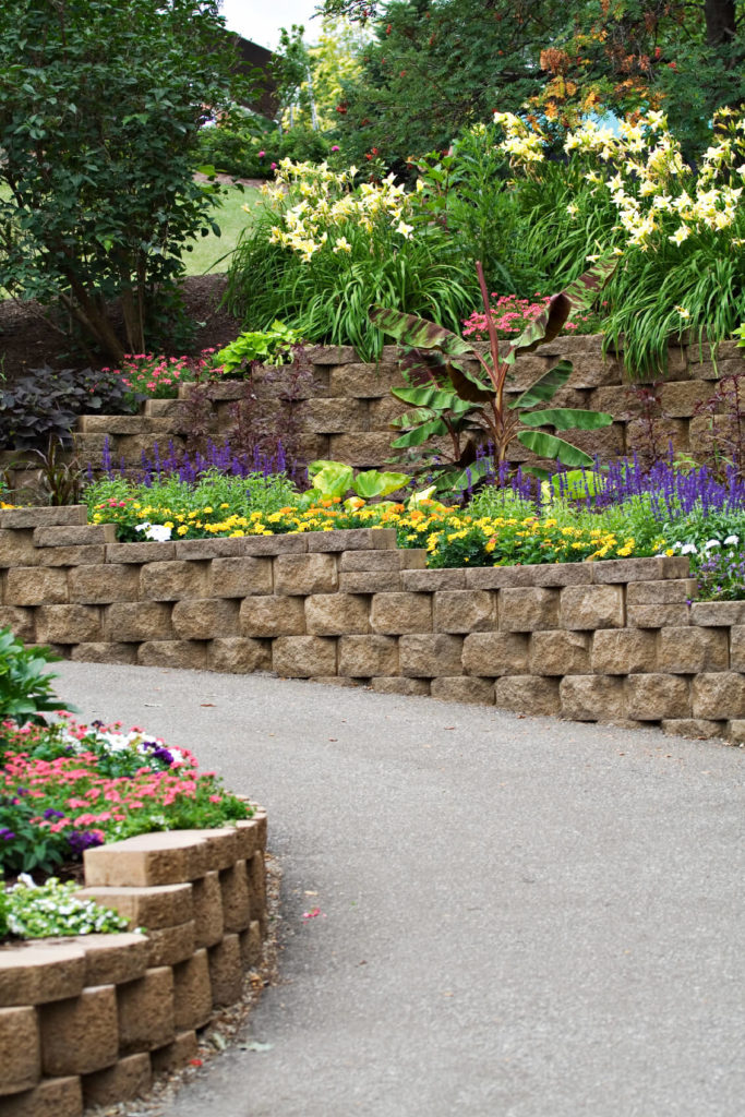 A Retaining Wall With Two Tiers Of Landscaping That Follows Paved Pathway