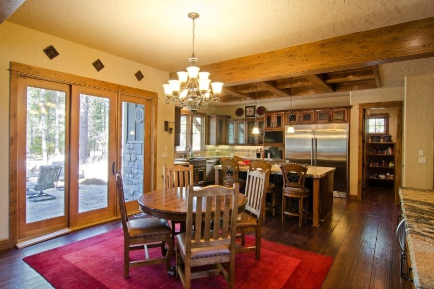 The kitchen with a small dining room between the doors to the back deck and the buffet and home bar. A bright red rug in two shades brightens the light room. A small door leads into the pantry from the right of the enormous refrigerator.