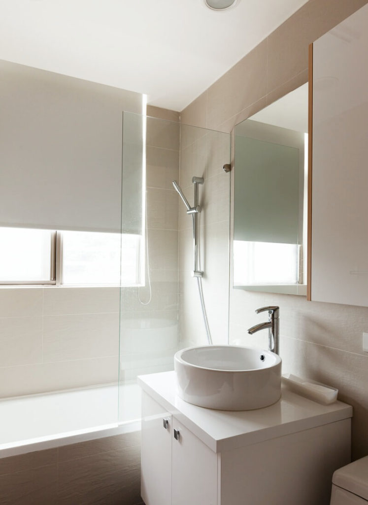 The modestly-sized bathroom has a deep vessel sink and a shower-bathtub combo with chrome fixtures. The outside of the bathtub is in textured beige tile.
