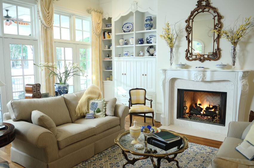 A small living room with an ornate fireplace mantle and a screened wood-burning fireplace. White built-ins to the left of the fireplace are perfect for displaying ceramics. French doors and windows along the back wall let in ample natural light to the contemporary, yet traditional space. Light blues are brought in by the rug, pillows, and other small accents. Glass vases grace the ornate mantle.