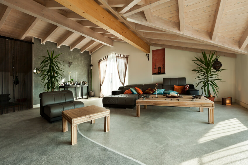 The wide-open space of this attic has been converted into a modern living space with a large entertaining area. The sloping roof lowers to the right, and curtains separate the space visually.