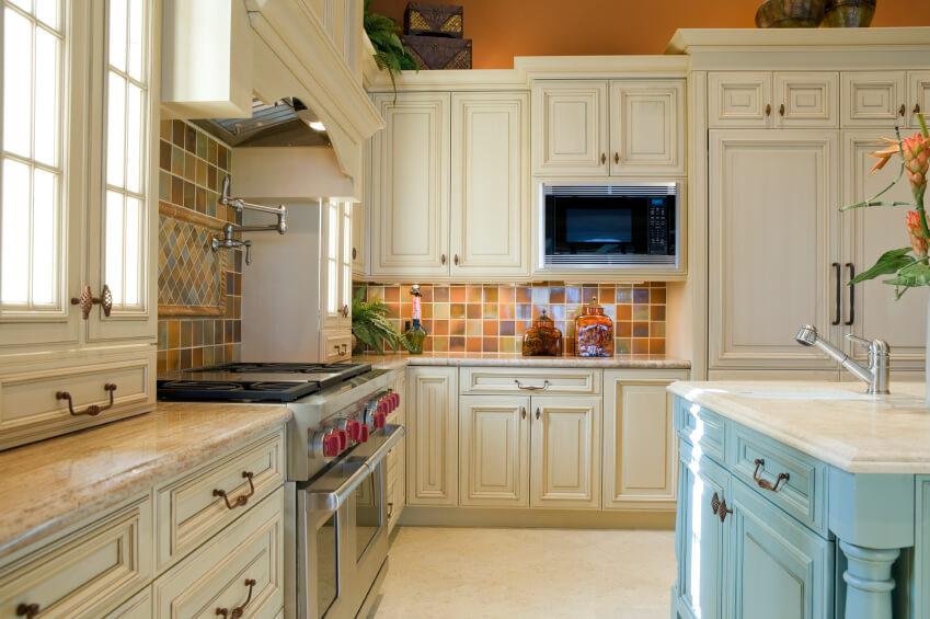 A Country Kitchen With A Light Blue Island And Multicolored Ceramic Tiles  For The Backsplash.