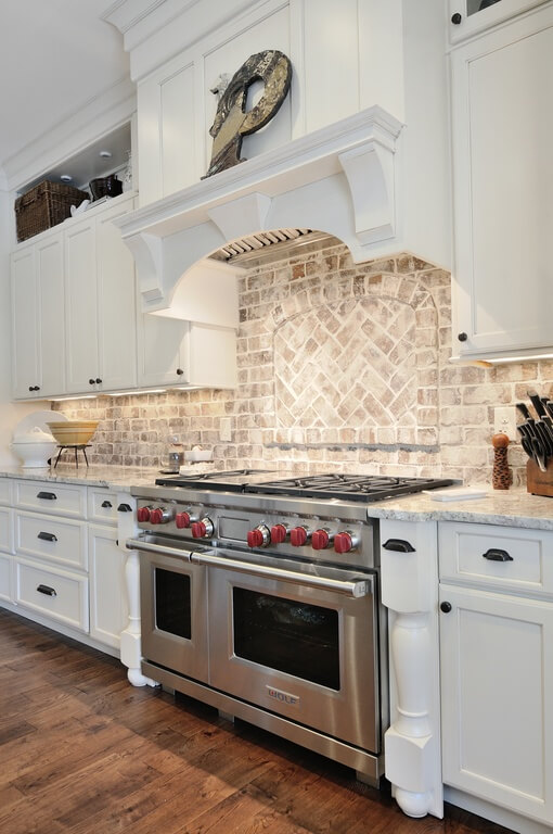 A Light, Aged Brick Backsplash With An Inset Center Design With A Chevron  Pattern.