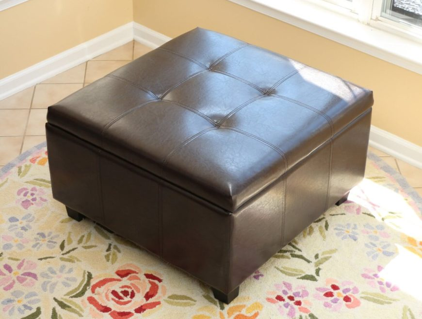 This square espresso-toned storage ottoman sits above a floral rug on tile flooring, adding a dark contrast to the light space. Button tufted cushioning on the lid conceals the abundant storage within.