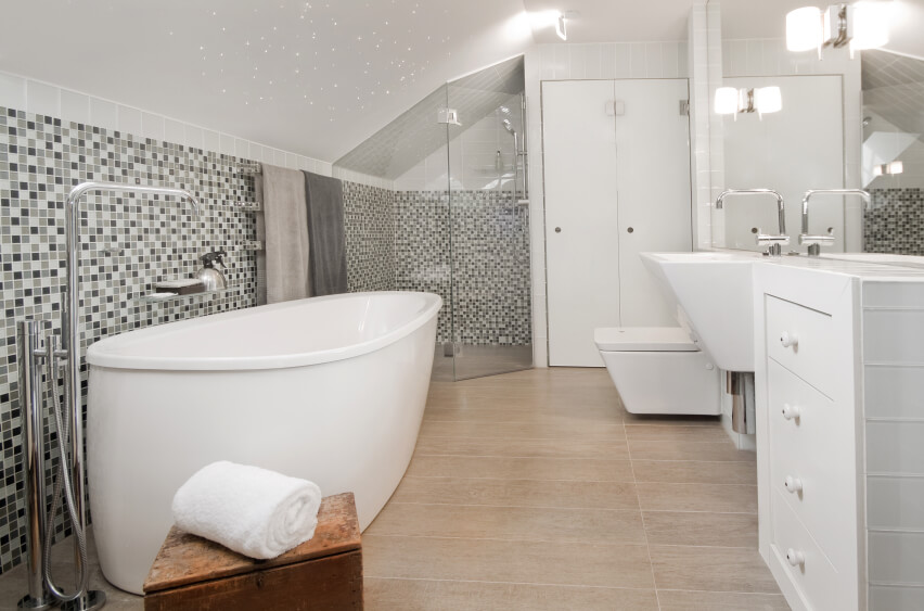 A spacious attic bathroom in gray and white with a large swath of glass mosaic tile beneath the slanted roof. A deep wall-mounted sink sits next to a chest of drawers. On the left is a long, deep soaking tub. The glass-enclosed shower stall in in the corner.