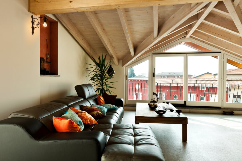 Enormous windows have been installed beneath the eaves of this attic, keeping the space from becoming dingy and dark. This attic has a faux leather sectional with reclining sections.