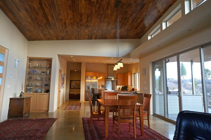 The high ceilings are hardwood, while the floors are a very light tile. A small, simple light fixture hangs from the high ceiling above the modestly sized dining set. Traditional-style red rugs add a bit of warmth to the room. In the corner, a built in curio cabinet is in light wood.