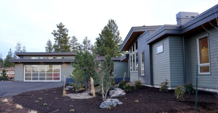 The landscaping is hardy and minimal, for easy care. A series of small pines are the largest bit of landscaping. The dusky blue siding on the hope is matched with a darker, richer blue trim.