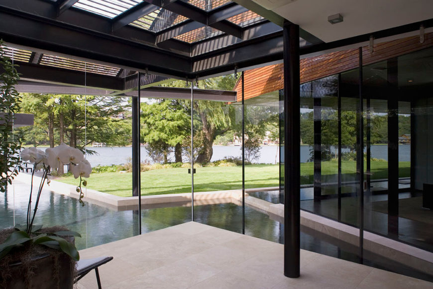 The solarium has glass panels from floor-to ceiling and a glass ceiling that is covered by wooden slats. The rear exterior of the home has a lengthy pool complex with multiple levels. A water feature leads into the main pool via a tiny waterfall. The solarium takes full advantage of the lakeside view and grand trees on the waterfront.