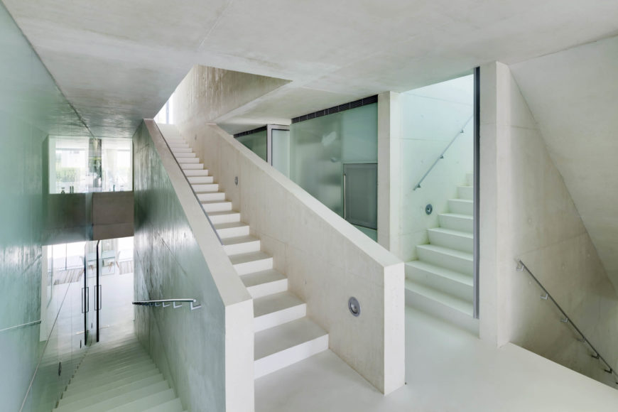 """Here's the central """"slow"""" stair, winding through the center of the home. The mixture of white and aquamarine glass infuses the entire space with an airy calm."""
