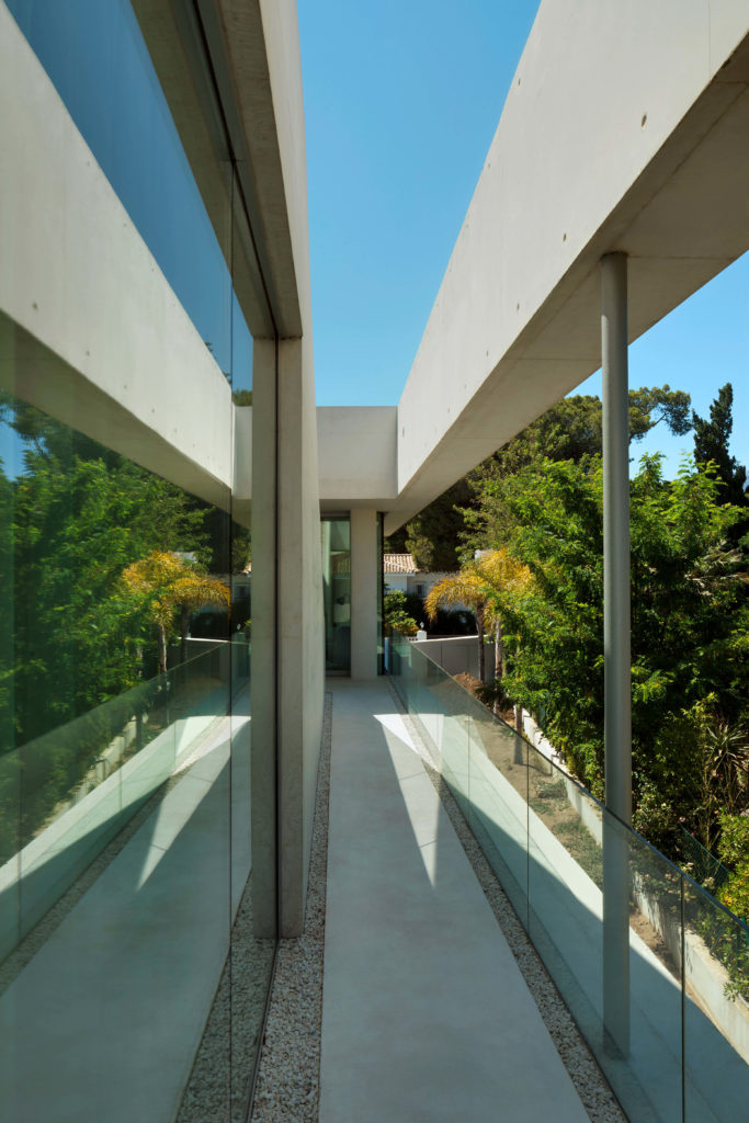 Moving around the side of the home, we see the sleek walkway and full height glass panels surrounding.