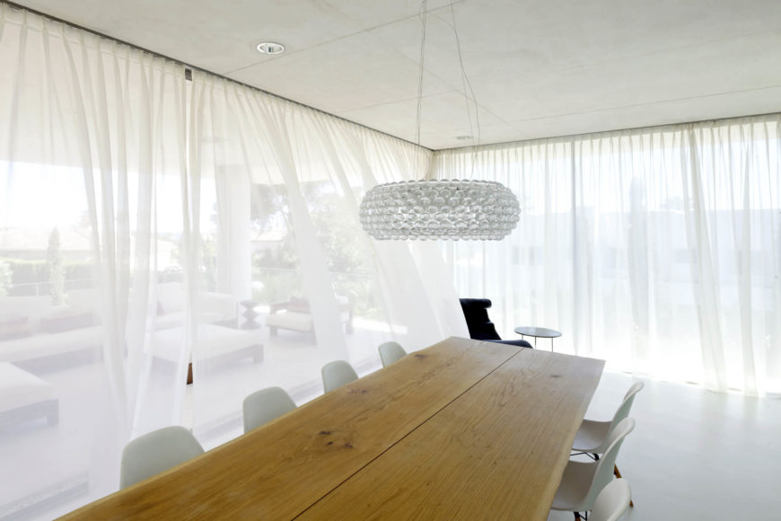 The lower level dining room features a large natural wood table surrounded by bespoke white chairs, in a space that opens entirely to the outdoors. Transparent curtains surround the room.