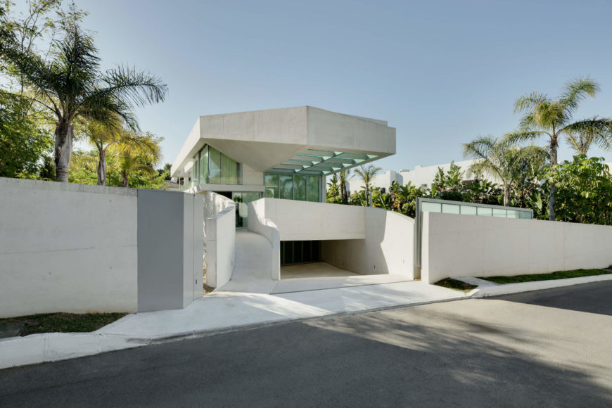 The angular project is obscured behind a long low wall and glass-panel sliding metal gate, its glass-bodied form rising above the greenery. The parking situation resides beneath the structure of the home.
