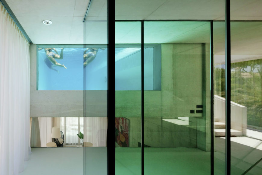 This view reveals the voyeuristic window into the pool as seen from the kitchen. Sunlight filters into the home through the water for a surreal effect.