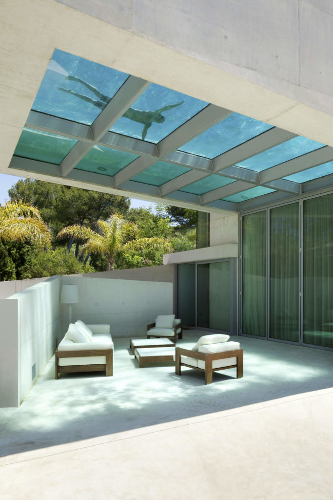Here we can see the furnished, sheltered patio space, with natural wood frame seating with white cushions standing in contrast to the concrete and glass surroundings.