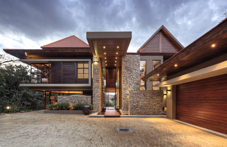 The front entry is a series of large stone brick pieces, framing a two story doorway wrapped in glass. Intricate brick driveway leads to garage enclosed in rich wood paneling.