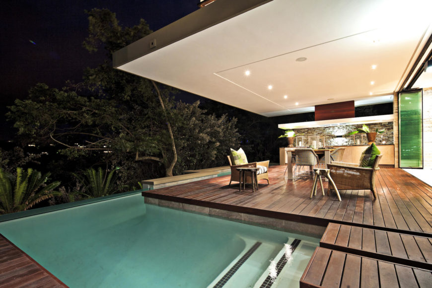 The furniture filled patio space beneath the bedroom houses a full bar countertop. Retractible glass panels open this area to the living room.