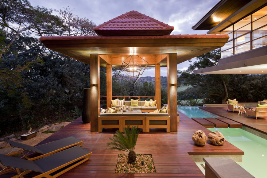 At dusk, the gazebo glows, mirroring the look of the home itself. A small zen garden is seen in foreground, while larger example rests below the patio, at left.