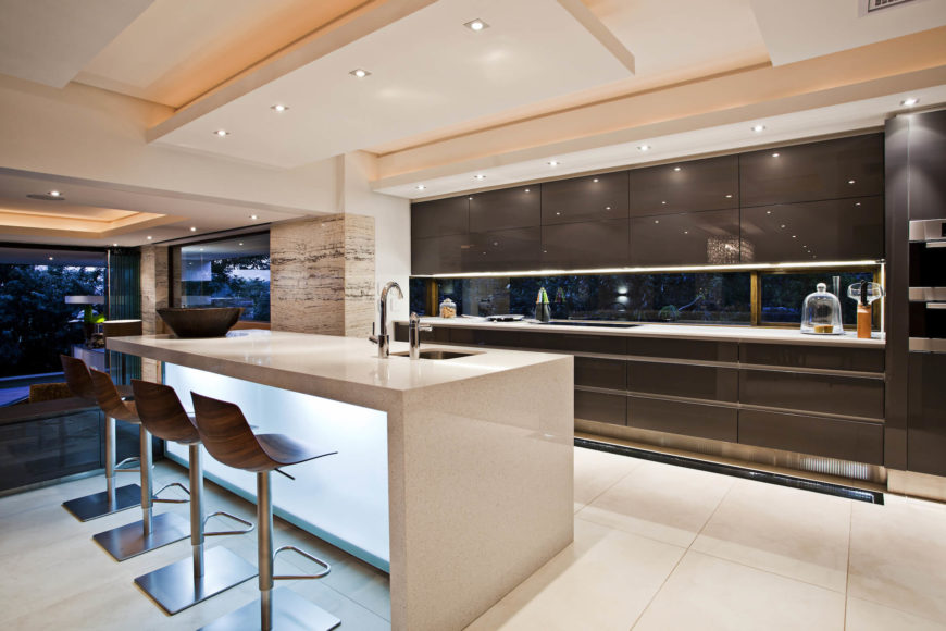 The kitchen features a massive granite topped island with glowing smoked glass body. Dark toned sleek cabinetry panels add contrast and elegance.