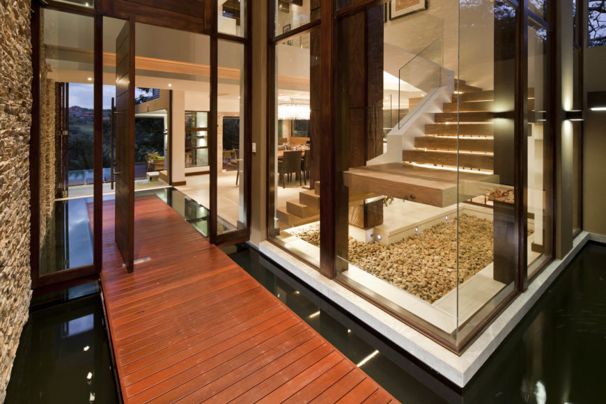 One enters the home via this warm toned wood platform wrapped in glass. The entire exterior is a series of large glass panels framed in deep hued timber.
