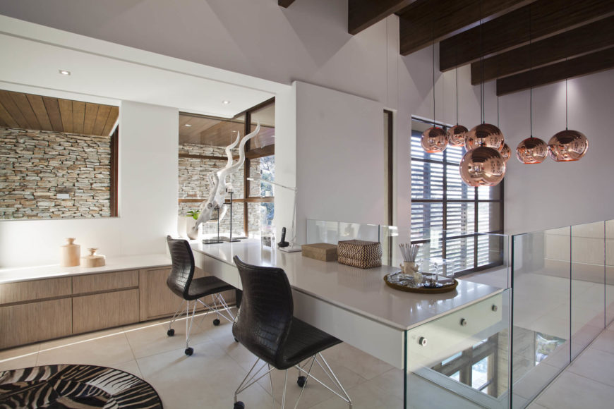 Moving upstairs, we see this glass wrapped walkway leading toward an open design office space. Floating white desk is paired with black seat, wire-frame chairs beside an arrangement of bronze sphere lighting.