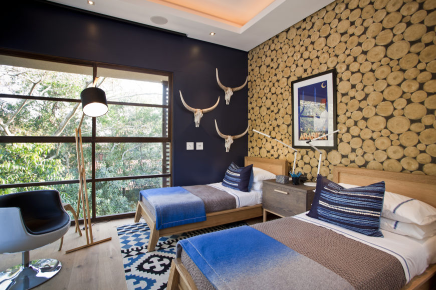 Marvelous bedroom accented with round wood cutouts wall and skull head wall decor mounted on the black wall. It has two beds that sit on a blue patterned rug.
