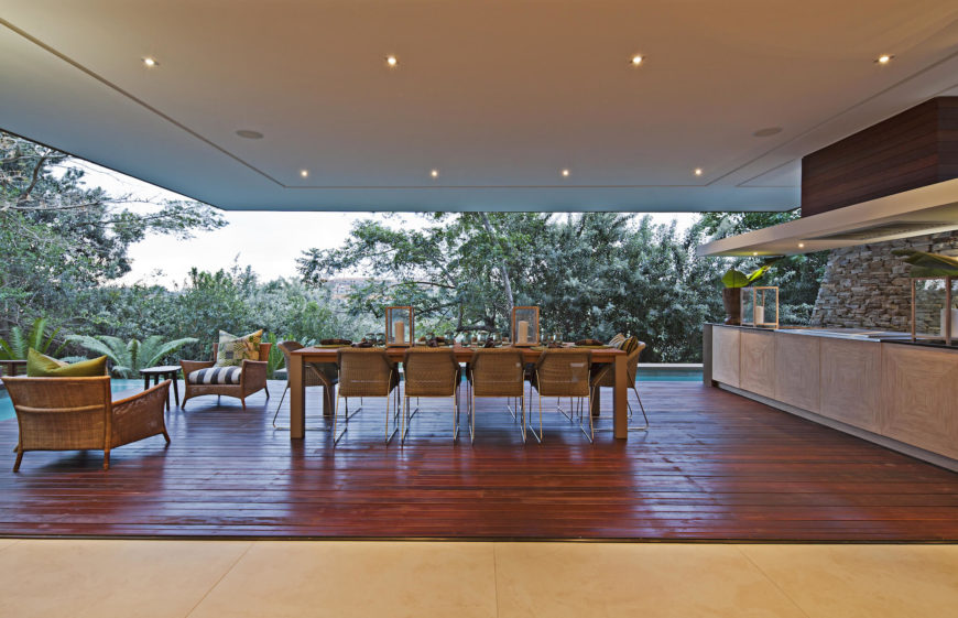 The patio dining area is lit via series of ceiling embedded lights. Lengthy wood dining table surrounded by wicker seating stands next to the large countertop equipped with a built-in range.