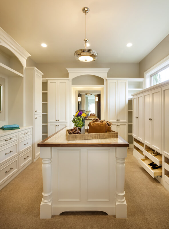 The walk-in closet has drawers for shoe storage, a storage island in the center, and full length mirrors on the back wall. The soft carpet is in a light beige.