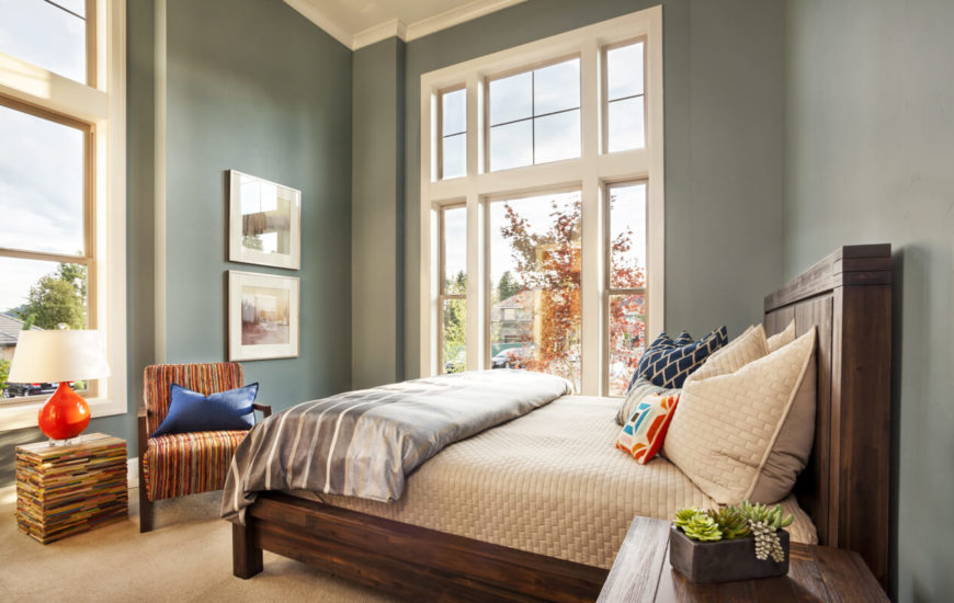One of the bedrooms in the home in a light blue-gray. The textured bedding is coupled with a silky gray bedspread. Bold orange is used as an accent color in the chair, throw pillows, and lamp.